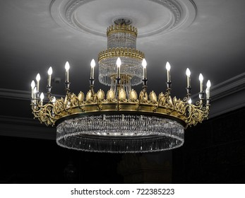 Old vintage chandelier with light candles in a palace ceiling, living room.