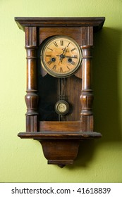 Old vintage clock hanging on green wall