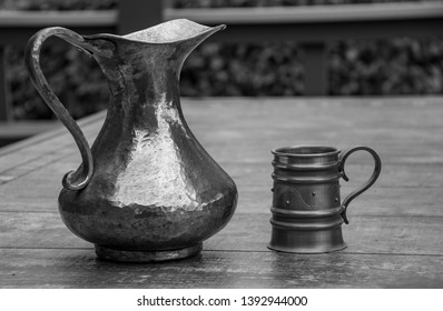 An Old Vintage Copper Pitcher and Pewter Mug Shot in Black and White