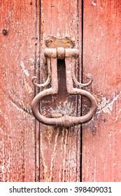 Old vintage door knocker on an old red wooden door