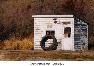 Old vintage gas house building with tire and peeled paint