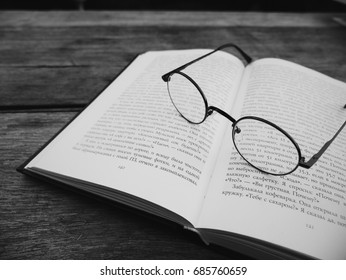 Old vintage glasses and notebook on wooden background