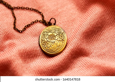 old vintage grandma's bronze locket on a pink fabric texture