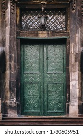 The old vintage green wooden door on the facade of the baroque Dominican Cathedral in Lviv is decorated with decorative forged flowers. Lamp and lattice window above the doorway.