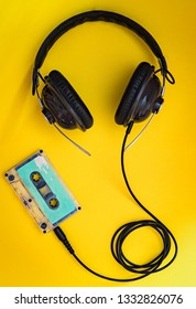 Old vintage grungy cassette tape and headphones on yellow colour background
