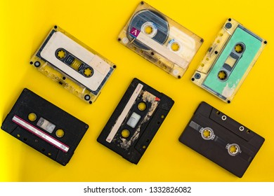 Old vintage grungy cassette tapes on yellow colour background
