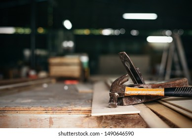 old vintage hammers and hallmark steel punches on a rustic wooden workbench of a goldsmith against a dark background,