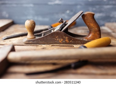 Old vintage hand tools on wooden background. Focus on jack-plane. Carpenter workplace.