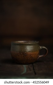 Old Vintage Handmade Clay Cup on Wood Table