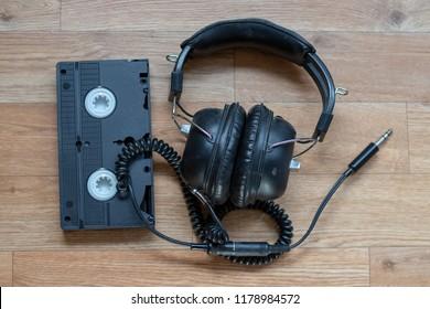 Old vintage headphones beside a black videocassette