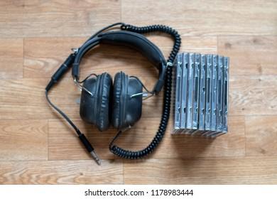 Old vintage headphones beside some CDs