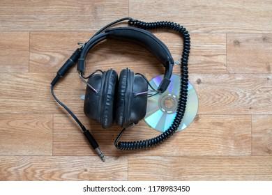 Old vintage headphones on top of a CD