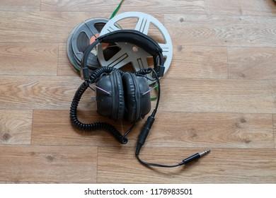 Old vintage headphones on top of old film rolls