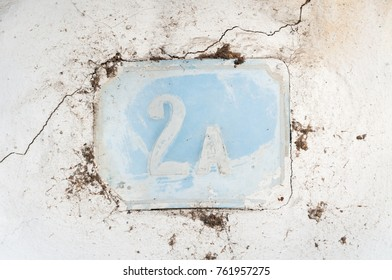 Old vintage house number 2a on the blue metal plate mounted on the white wall of abandoned house