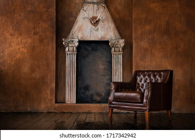 An old vintage hunting room and a wall with a fireplace made of columns, deer antlers hanging like a trophy. Leather vintage armchair in the interior.