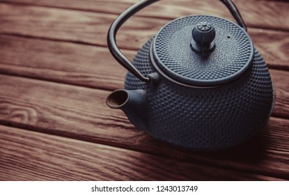 Old vintage iron teapot on a wooden background, top view.