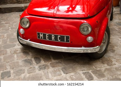 Old vintage Italian car in red with Merci written on the plate