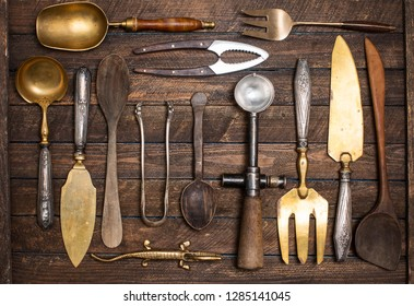 Old vintage kitchen utensils on wooden background.