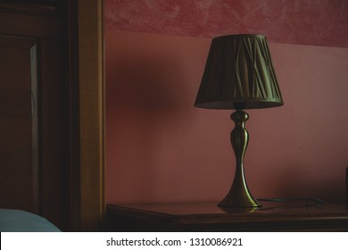 Old vintage lamp next to a bed, wooden base with cloth upper part. Hotel room interior with detail on a bed table lamp. Purple or pinky background in a hotel room.