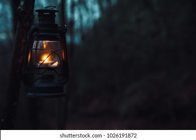 Old vintage lantern lit in the darkness of the woods