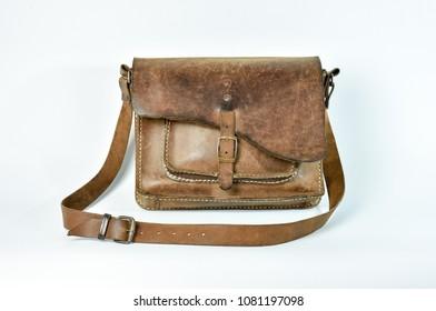 Old vintage leather shoulder bag for rider. Rustic design for tough field use leather bag. Shot on white background.