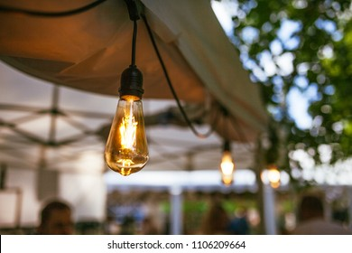 Old vintage light bulb hanging from roof of tent, lights at summer festival