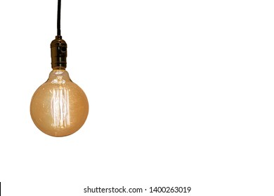 An old vintage light bulb on white background. Old shining glass bulb with orange and yellow light. Space for copy. Light bulb on a wire.