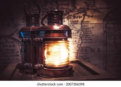 Vieille lanterne lumineuse vintage avec vieille carte antique sur fond d'aventure