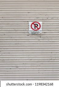 Old, vintage metal door or fence with no parking sign in Litochoro Greece, english translate of text is ''parking prohibited''