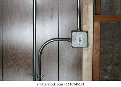 Old vintage metal electricity switch and junction box with exposed conduit pipes on the surface mounted on a wooden wall alongside a door