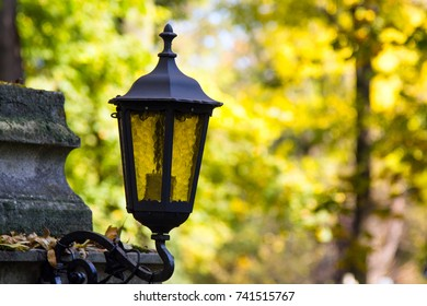 Old vintage metal lantern on autumn trees background. Shallow depth of field