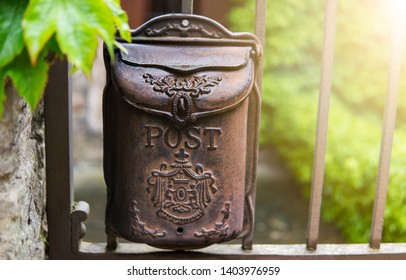 Old vintage metallic mailbox or postbox with soft unfocused background with green bushes and sunlight