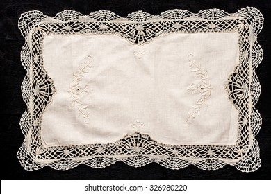 Old vintage napkin with lace border on the black wooden table