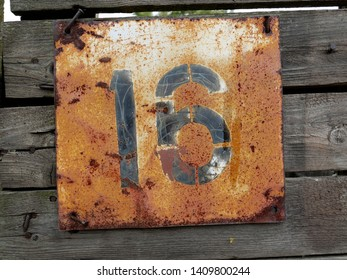 Old vintage number sixteen door plate on old wooden fence. House number sixteen