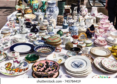 Old vintage objects and furniture: porcelain plates, saucers, cups, vessels, vases, teapots at a garage sale at the flea market in Paris. France