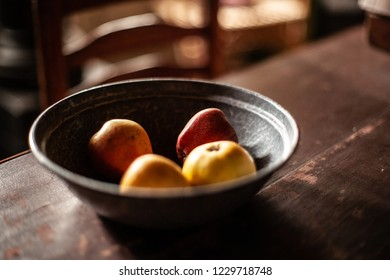 Old vintage pewter bowl with fresh colorful apples. Fruit on scale with rembrandt light in a traditional still life scene