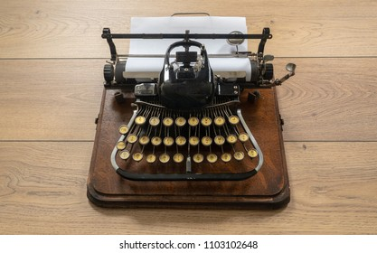Old vintage portable typewriter with non qwerty type keys on wooden desk