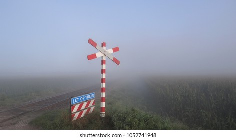 An old vintage railroad crossing in the Netherlands with thick fog.