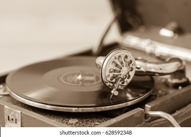 Old vintage record player vinyl records gramophone (phonograph) on a wooden background, closeup