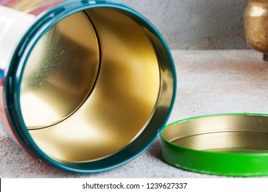 Old vintage red green tin canister and green plants in brass flower pots on concrete background. Copy space for text.
