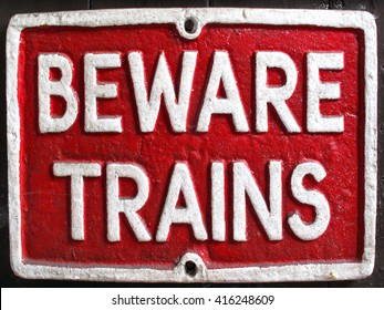 Old vintage red retro distressed railway enamel metal sign with text, beware trains
