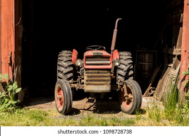 Old Vintage Red Tractor Coming Out of Old Wooden Red Barn