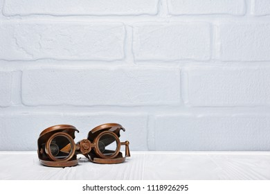 Old vintage retro binoculars as an accessory for styled journey with copy space on gray brick wall background