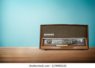 Old vintage retro broadcast radio on wood table with mint blue background .