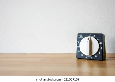Old vintage retro classic kitchen timer. Wood surface. White wall background and warm autumn natural light.
