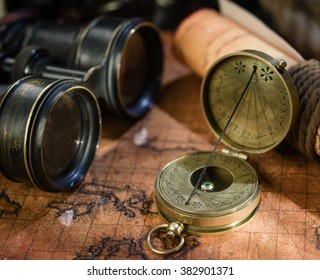 Old vintage retro compass and binoculars on ancient world map. Travel geography navigation concept background. Vintage still life.