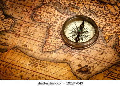 Old vintage retro compass on ancient map. The map used is in Public domain. Map source: Library of Congress. Country: Belgium Year: 1570. Author: Abraham Ortelius (1527-1598)