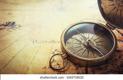 Old vintage retro compass on ancient map background. Travel geography navigation concept background.