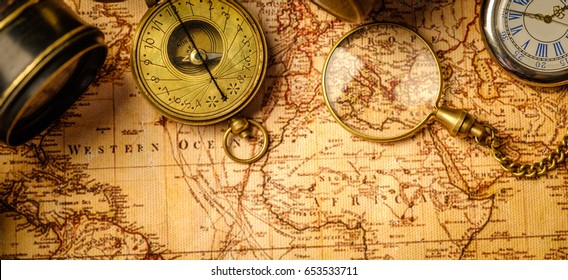 Old vintage retro compass and spyglass on ancient world map. Vintage still life. Travel geography navigation concept background. Top view.