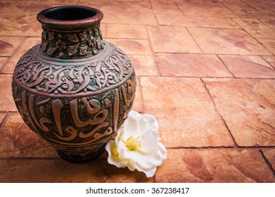 Old vintage retro hand made Islamic style vase with muslim ornaments on a brick background with white rose flower, beautiful arabian jar photo, ramadan kareem